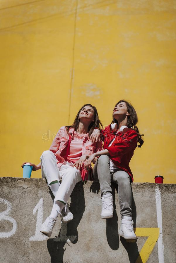 Two happy girls sitting together on parapet. Urban lifestyle concept. Full length portrait of two pretty happy smiling ladies in casual stylish clothes resting stock photos