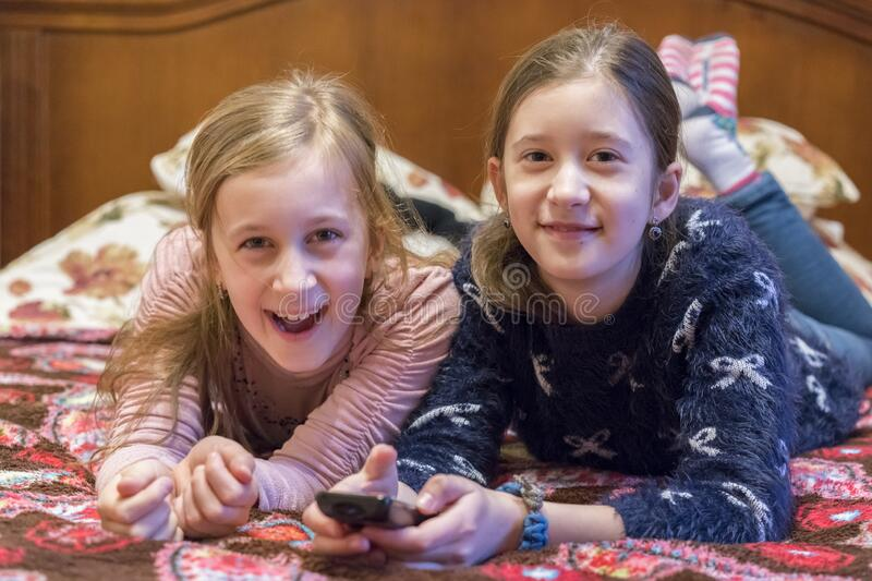 Two happy girls watching tv or movie. A horizontal photo of two young pretty smiling sisters lying on bed and watching their stock photo