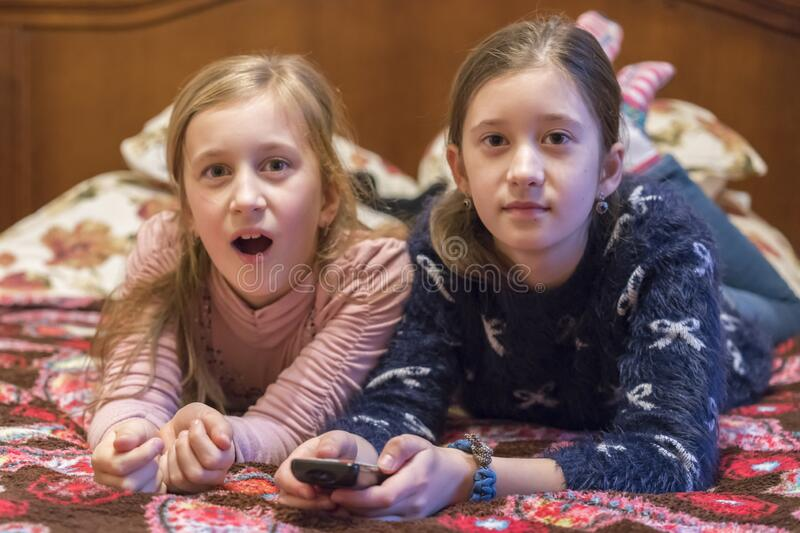 Two happy girls watching tv or movie. A horizontal photo of two young pretty smiling sisters lying on bed and watching their royalty free stock photo
