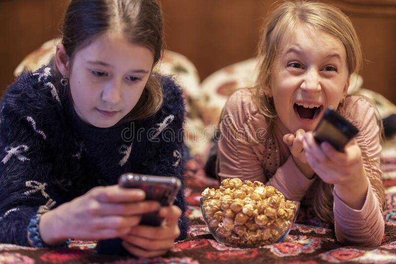 Two happy girls watching tv or movie with popcorn. A horizontal photo of two young pretty smiling sisters lying on bed and stock photos