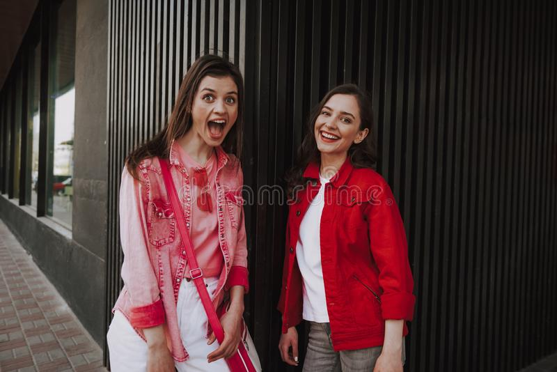 Two happy hipster girls having fun together. Urban lifestyle and activity concept. Waist up portrait of young happy excited stylish hipster ladies leaning stock photo