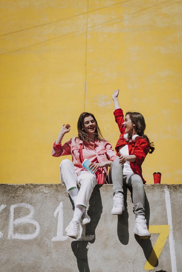 Two happy hipster girls sitting on parapet. Urban lifestyle concept. Full length portrait of two happy young hipster ladies having fun together on parapet with stock images