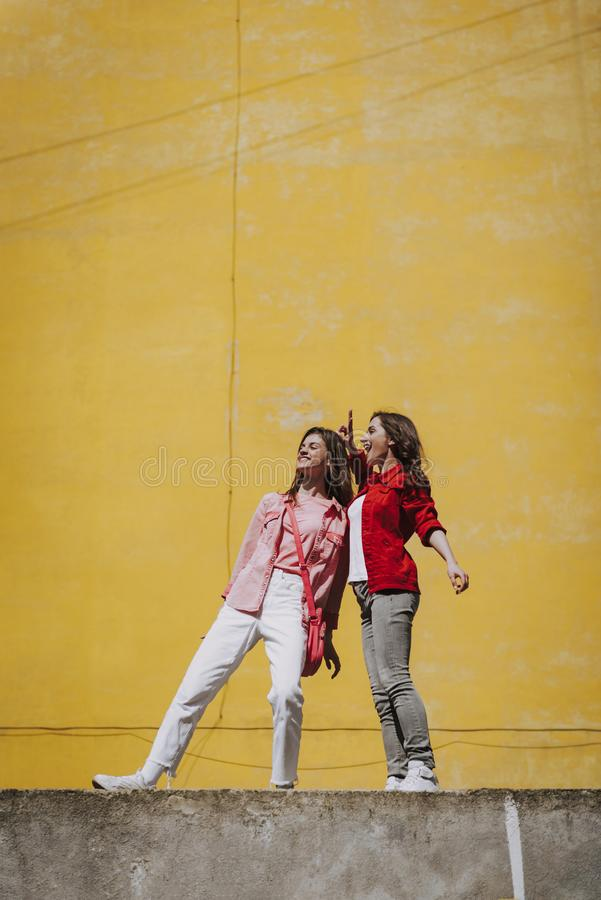 Two happy hipster girls staying on parapet. Urban lifestyle concept. Full length portrait of two happy young hipster ladies having fun together while staying on stock photos