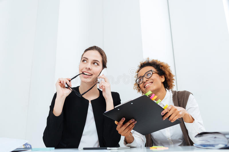 Two happy inspired businesswomen with clipboard dreaming and smiling stock photo