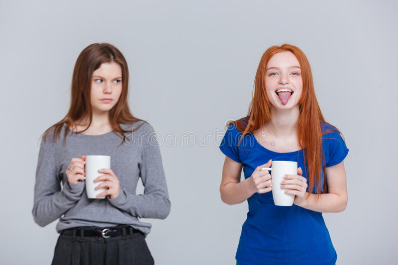 Two happy joking and sad frowning young women drinking tea. From mugs stock photo