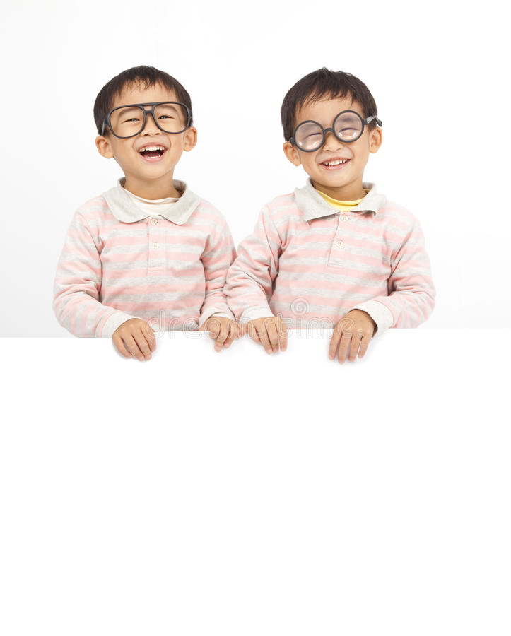 Two happy kids. Behind white board stock photo
