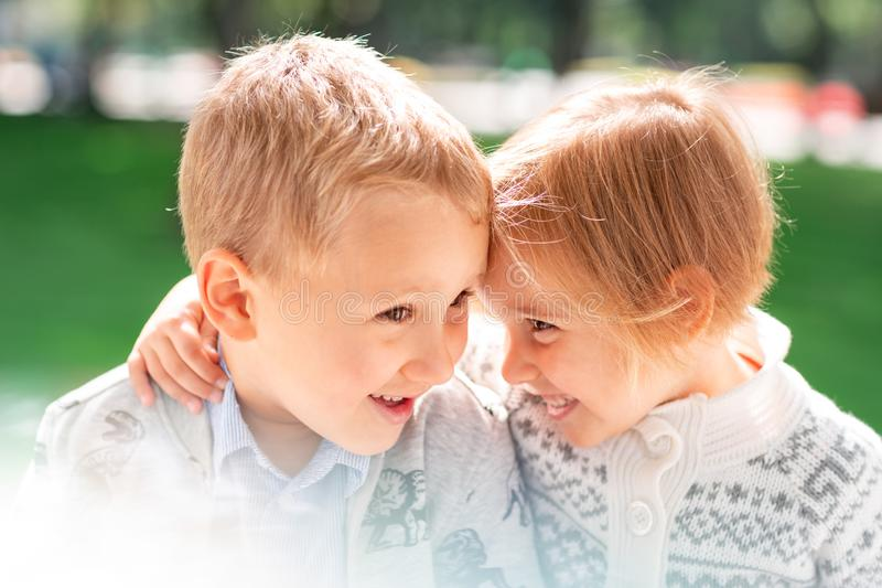Two happy kids boy and a girl hugging and smiling stock photography