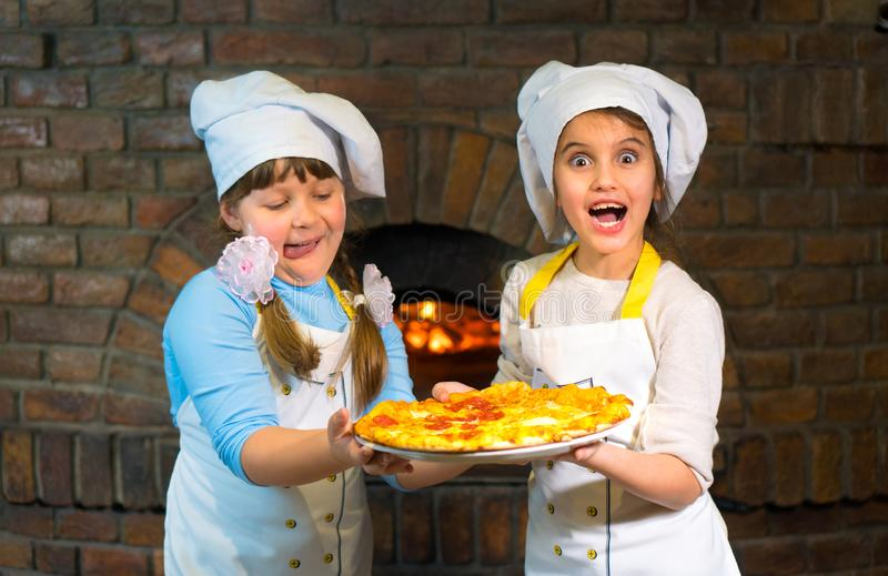 Two happy kids in chef hats hold pizza together on a stone stove background. stock photo