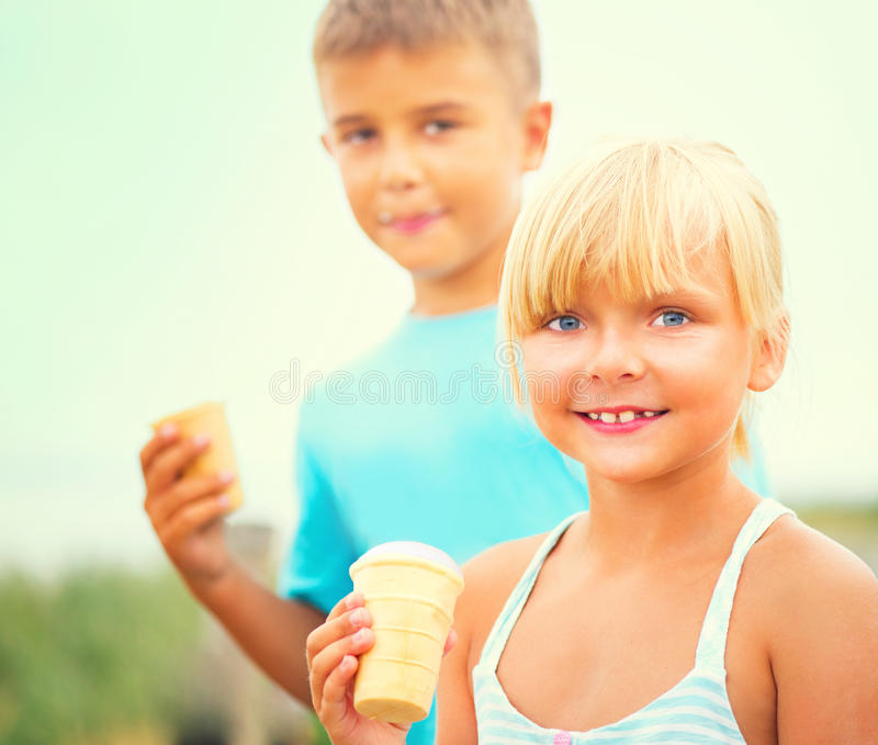 Two happy kids eating icecream outdoors royalty free stock images