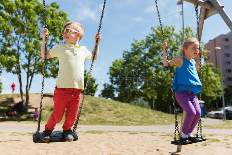 Two happy kids swinging on swing at playground. Summer, childhood, leisure, friendship and people concept - two happy kids swinging on swing at children stock photo