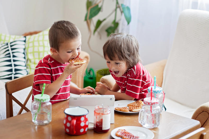 Two happy kids, two brothers, having healthy breakfast sitting a. T wooden table in sunny kitchen, eating waffles and watching cartoon on tablet royalty free stock image