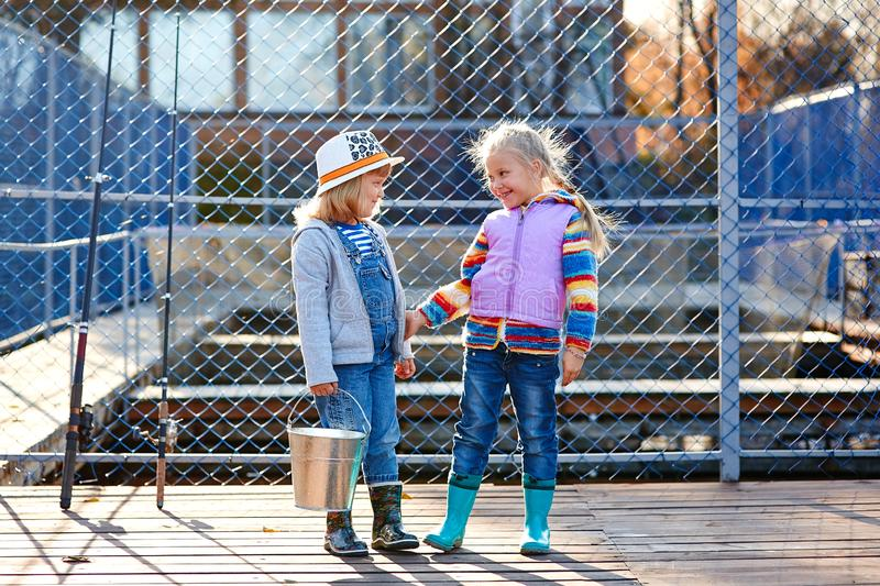 Two happy laughing children with fishing rods and a bucket on a fishing trip on a wooden pontoon on a fish farm stock photography