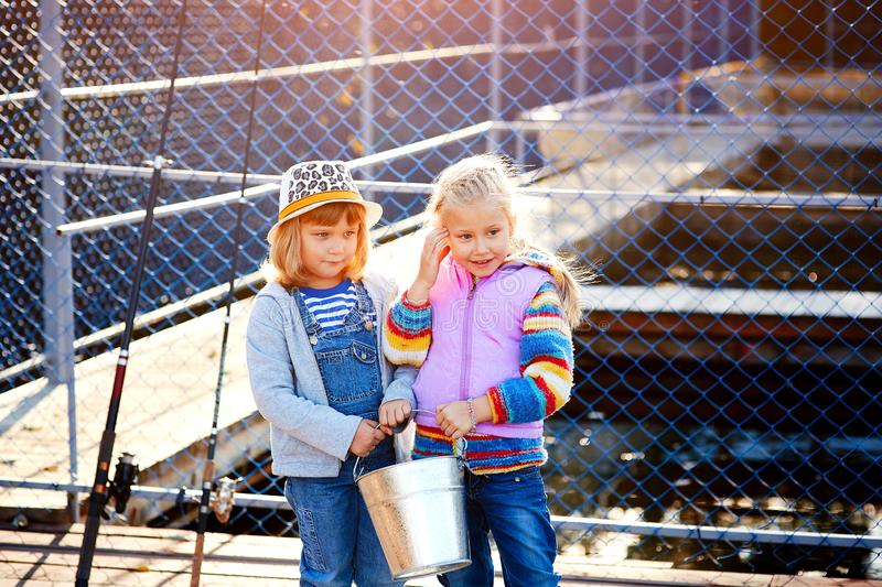 Two happy laughing children with fishing rods and a bucket on a fishing trip on a wooden pontoon on a fish farm stock image