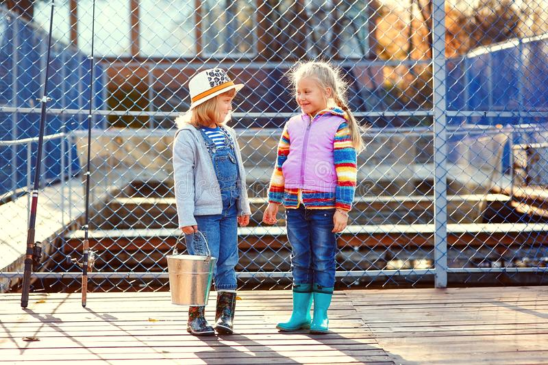 Two happy laughing children with fishing rods and a bucket on a fishing trip on a wooden pontoon on a fish farm stock images