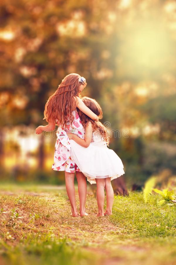 Two Happy little girl embracing and smiling at summer day, back stock photos