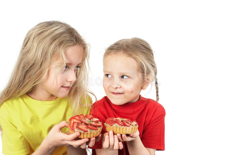 Kids eating fruit cakes royalty free stock photos