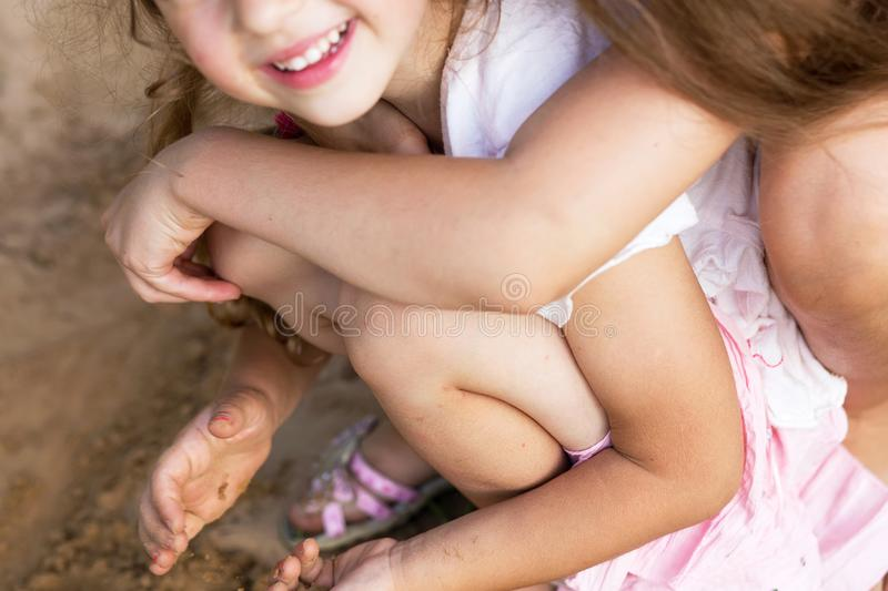 Two Happy little girls laughing and embracing at the summer par stock images