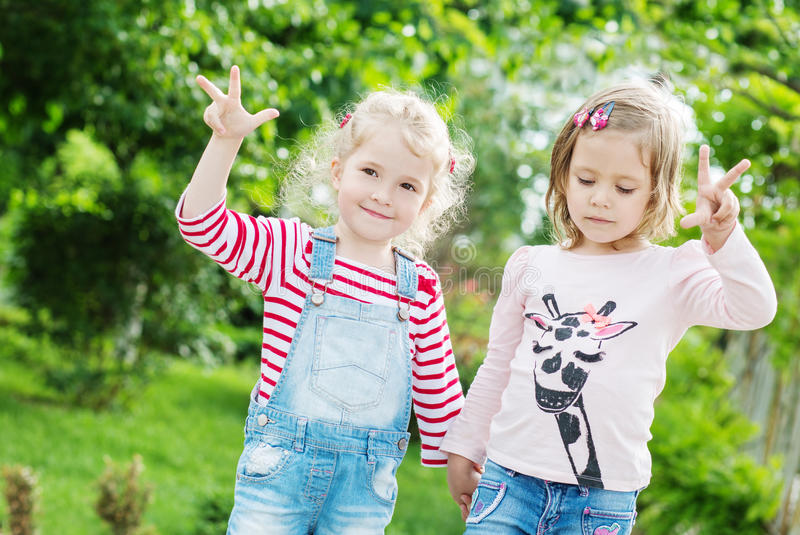 Two happy little girls in the park. Two happy little girls playing in the park stock photography