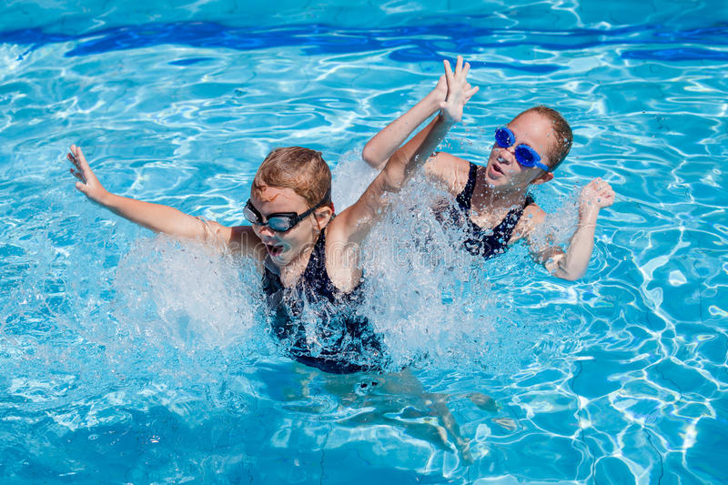 Two happy little girls playing in the swimming pool stock image