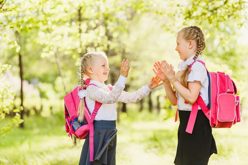 Two little girls Schoolgirls playing Patty-cake outdoors royalty free stock images