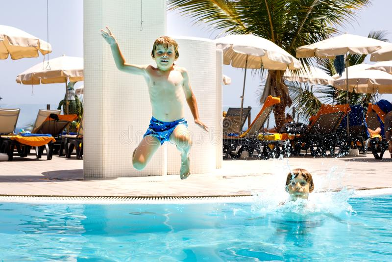 Two happy little kids boys jumping in the pool and having fun on family vacations in a hotel resort. Healthy children. Siblings and best friends playing in royalty free stock image
