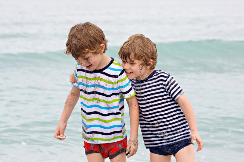 Two happy little kids boys running on the beach of ocean. Funny children, siblings, twins and best friends making royalty free stock image