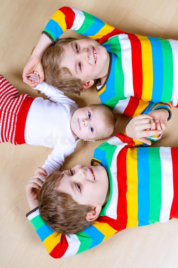 Two happy little preschool kids boys with newborn baby girl. Cute sister. Siblings, twins children and baby playing together. Kids bonding. Family of three royalty free stock photos