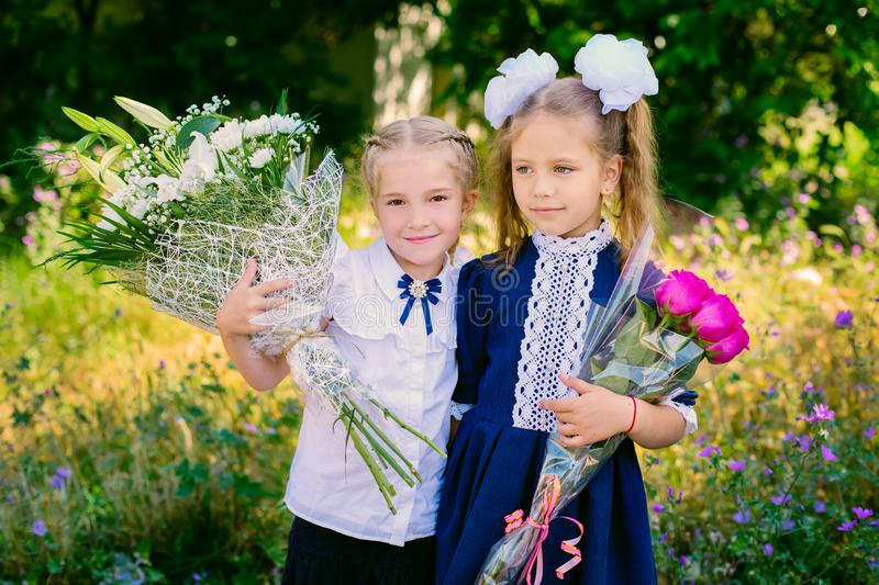 Two happy little schoolgirls with bouquets stock photo