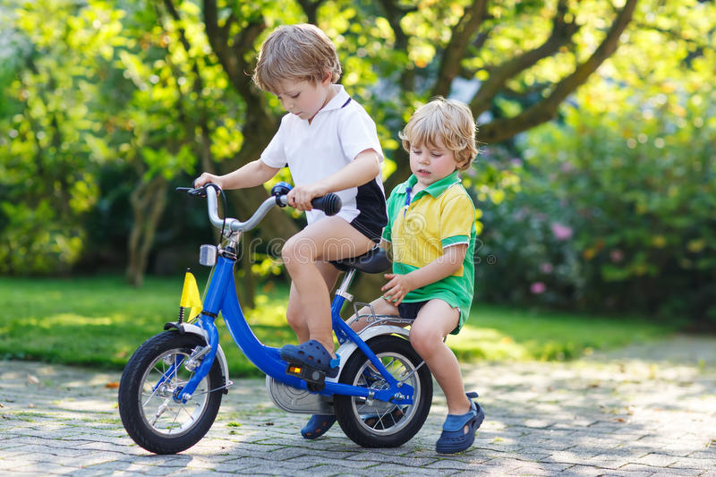 Two happy little sibling kids having fun together on one bicycle royalty free stock photo