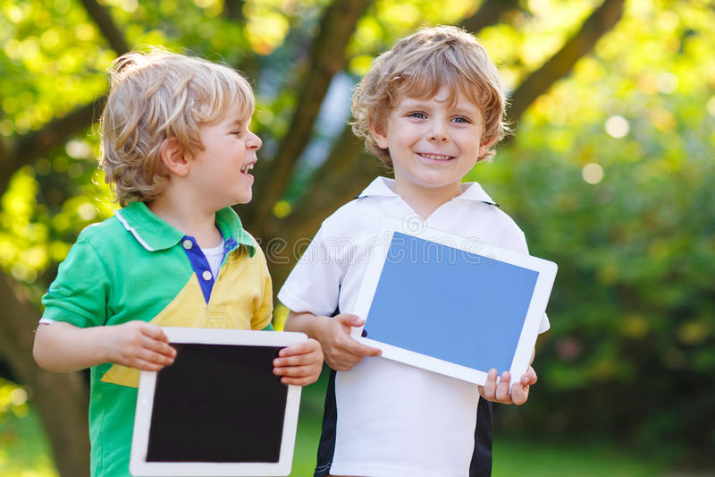 Two happy little sibling kids holding tablet pc, outdoors stock photos