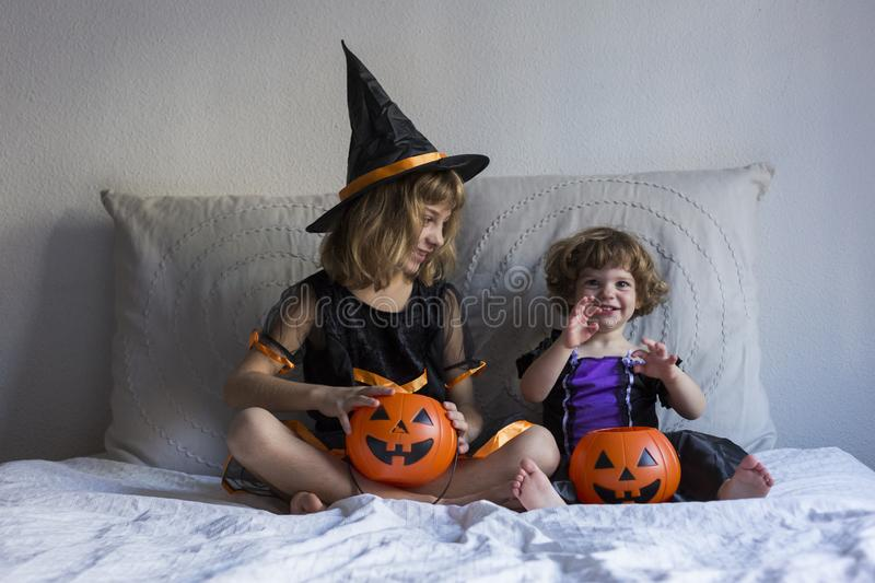two happy little sisters having fun at home wearing halloween costumes and pumpkins. Trick or treat. Home, indoors. Lifestyle stock photo