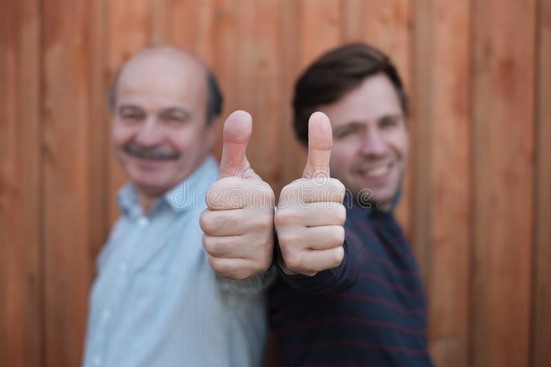 Two happy men giving thumbs up sign. Blurred photo. stock photo