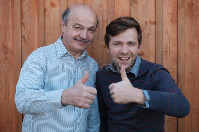 Two happy men giving thumbs up sign. stock photos