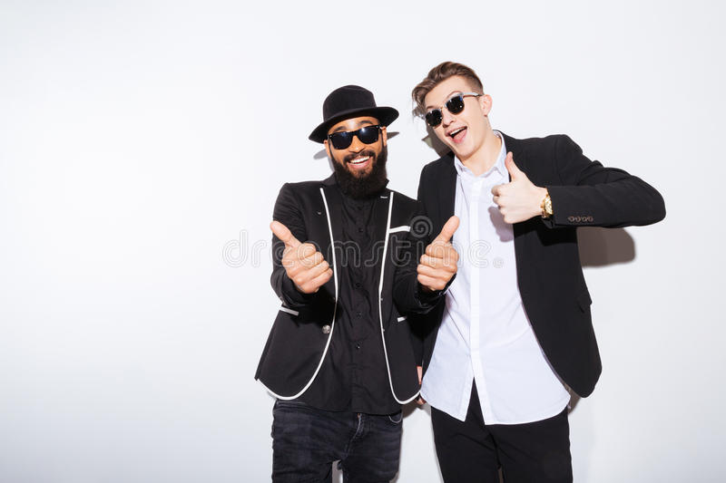 Two happy men standing and showing thumbs up royalty free stock image