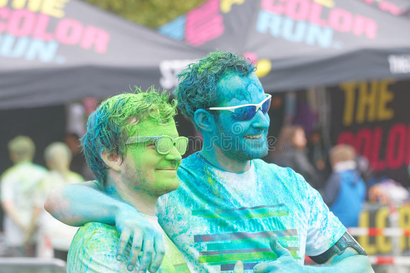 Two happy men wearing sun glasses covered with color powder stock photo