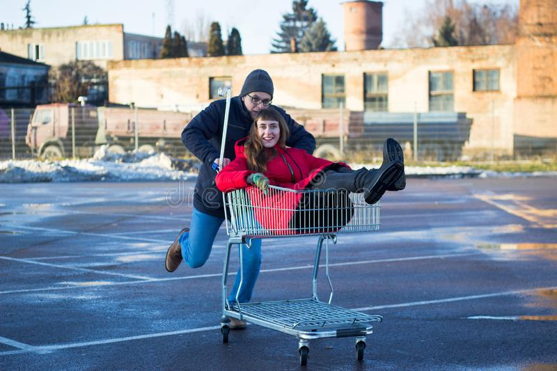 Two happy man and woman having fun at shopping cart outdoors stock photos