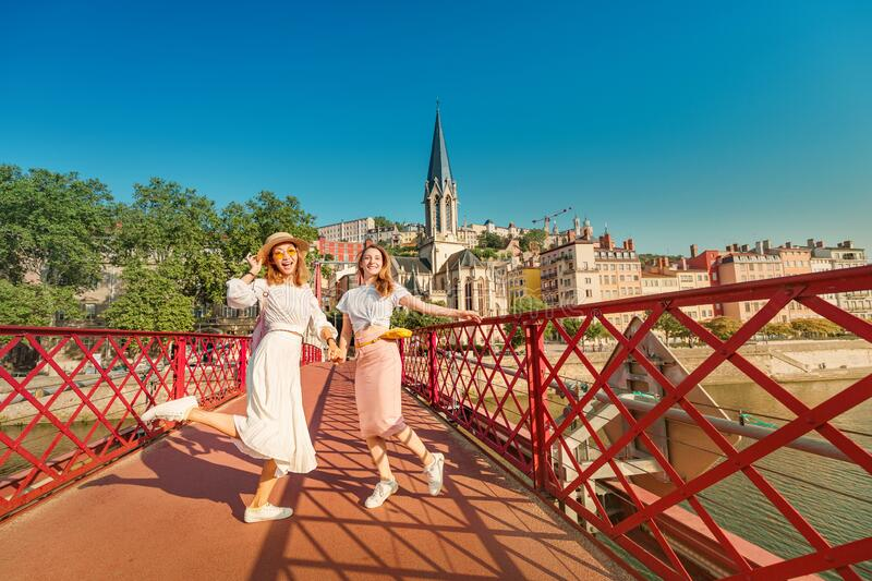 Happy mixed race girls having fun and jumping on a bridge, while travelling in Lyon city in France royalty free stock image