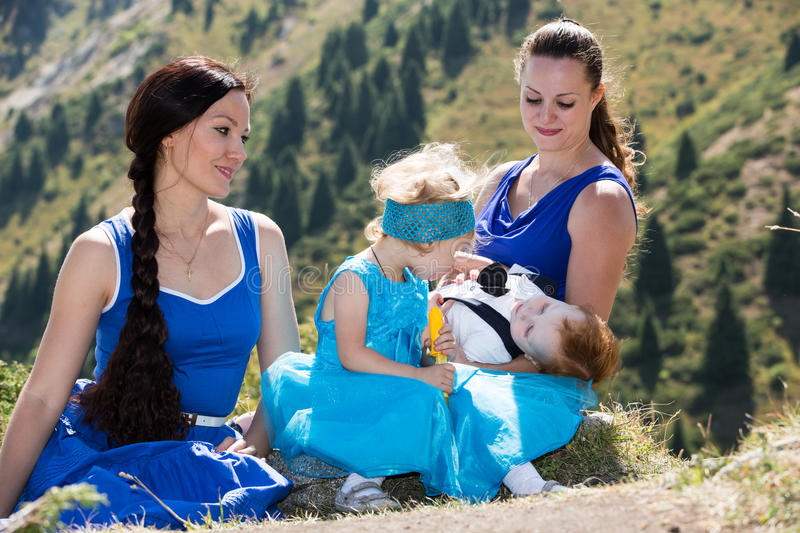 Two happy moms and children girl and boy hugging on nature stock photos