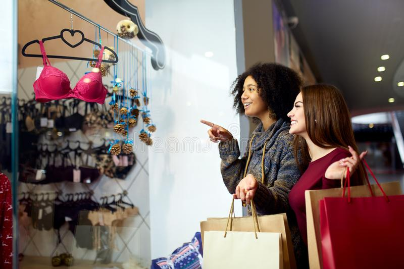 Two happy multiethnic young mixed race woman shopping for lingerie near clothing boutique shop window, decide whether to royalty free stock photos
