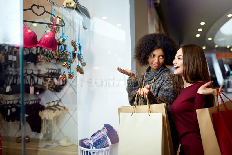 Two happy multiethnic young mixed race woman shopping for lingerie near clothing boutique shop window, decide whether to royalty free stock image
