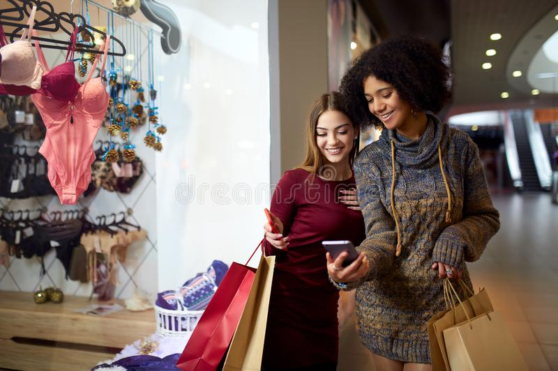 Two happy multiethnic young mixed race woman shopping for lingerie near clothing boutique shop window, looking at royalty free stock image