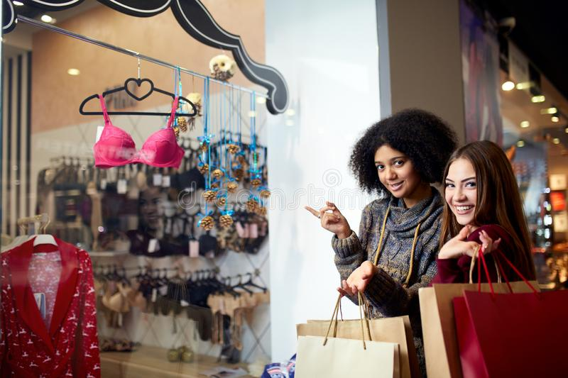 Two happy multiethnic young mixed race woman shopping for lingerie near clothing boutique shop window, decide whether to stock photo
