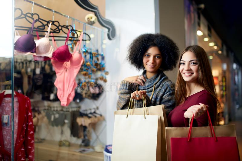 Two happy multiethnic young mixed race woman shopping for lingerie near clothing boutique shop window, decide whether to royalty free stock images