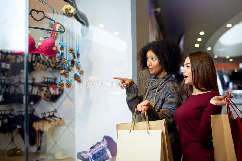 Two happy multiethnic young mixed race woman shopping for lingerie near clothing boutique shop window, decide whether to stock image