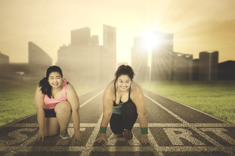 Two overweight women kneeling on the start line. Two happy overweight women ready to run while kneeling on the start line. Shot at sunrise time royalty free stock images