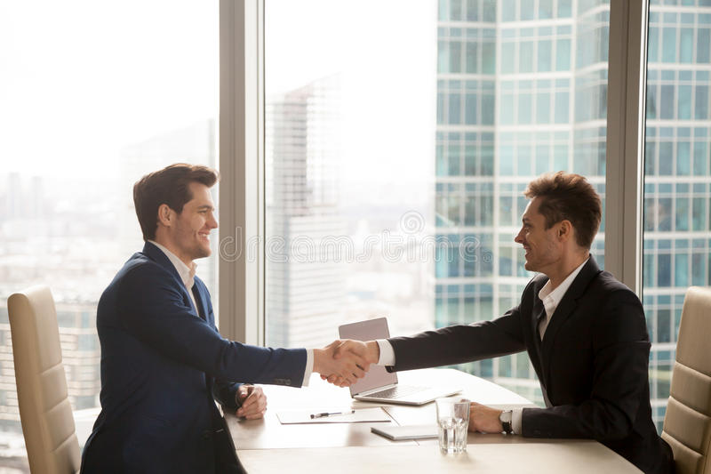Two happy satisfied businessmen handshaking in office, city at b. Two happy satisfied businessmen shaking hands over desk after successful negotiations, closing stock images