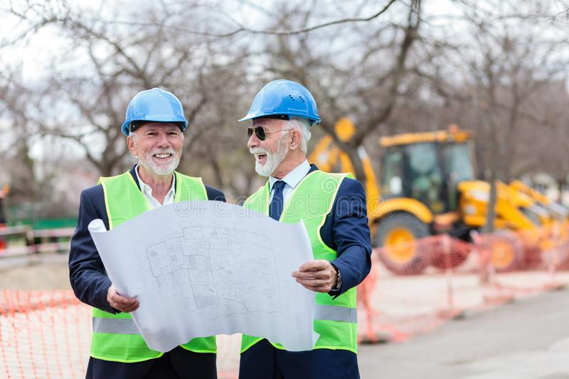 Two senior architects or business partners visiting construction site, looking at building blueprints. Two happy senior architects or business partners visiting royalty free stock photography