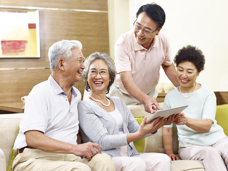Two happy senior asian couples using tablet computer at home. Two active senior asian couples looking at tablet computer, happy and laughing stock photo