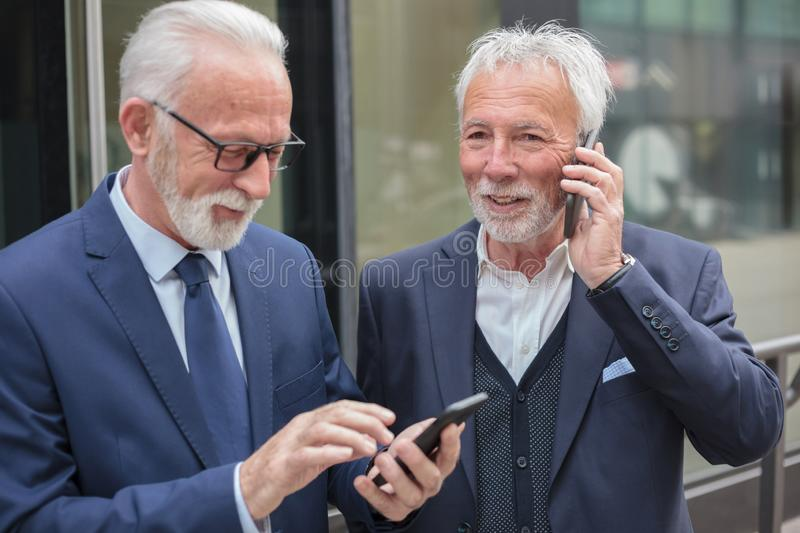 Two happy senior businessmen making phone calls, standing on the sidewalk royalty free stock images