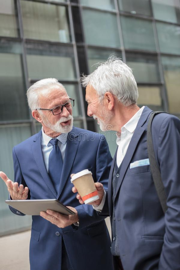 Two happy senior gray hair businessmen walking along the street during coffee break royalty free stock photography